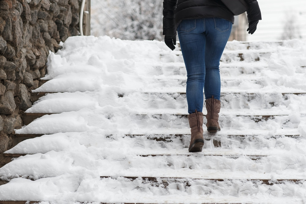 Woman walking up icy stairs