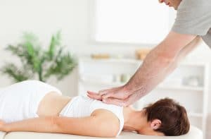 chiropractor adjusting female patients upper back