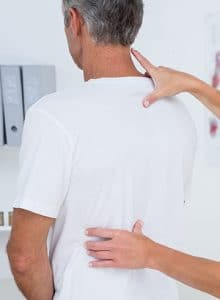 chiropractor looking at male patients back
