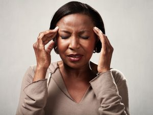 woman holding her head due to chronic headache