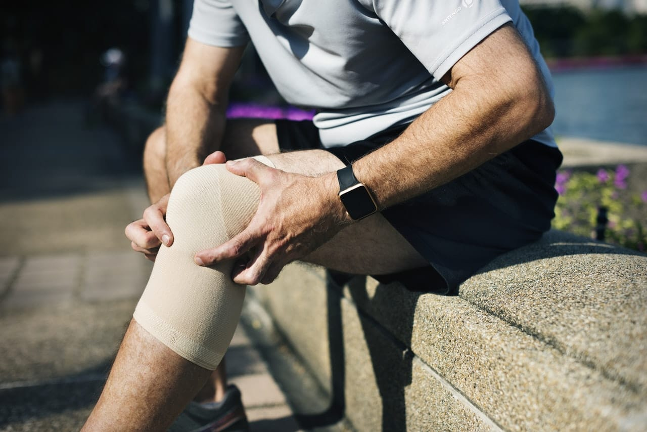 Sports Man holds knee seeking pain treatment in omaha
