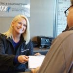 receptionist giving a patient paperwork