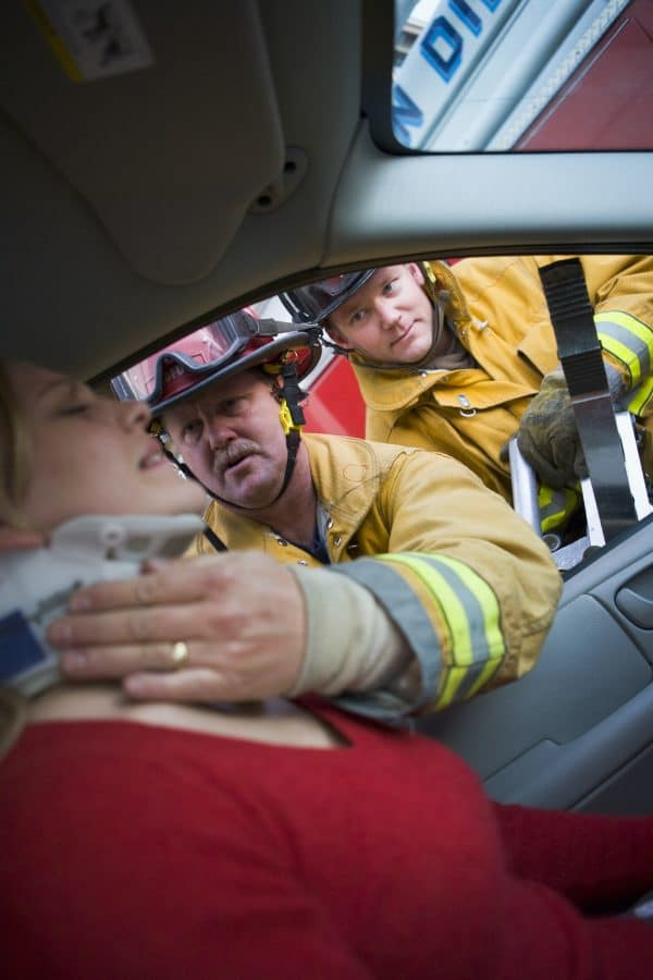 firefighters helping a female wwho had just been in a recent car accident