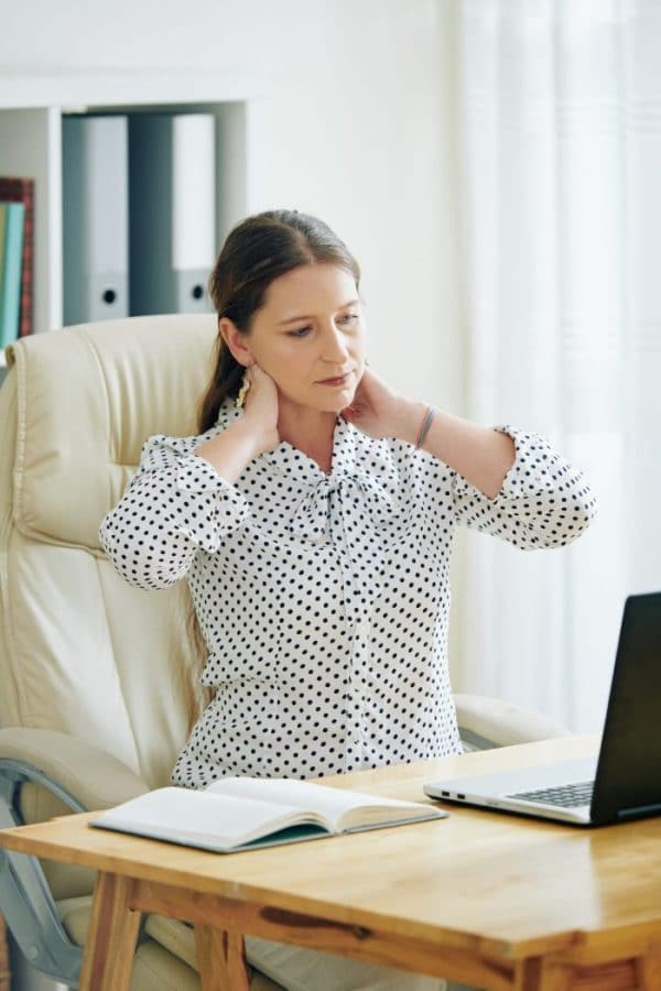 business woman holding her neck due to pain