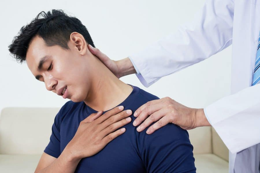 young man having his shoulder stretched due to pain