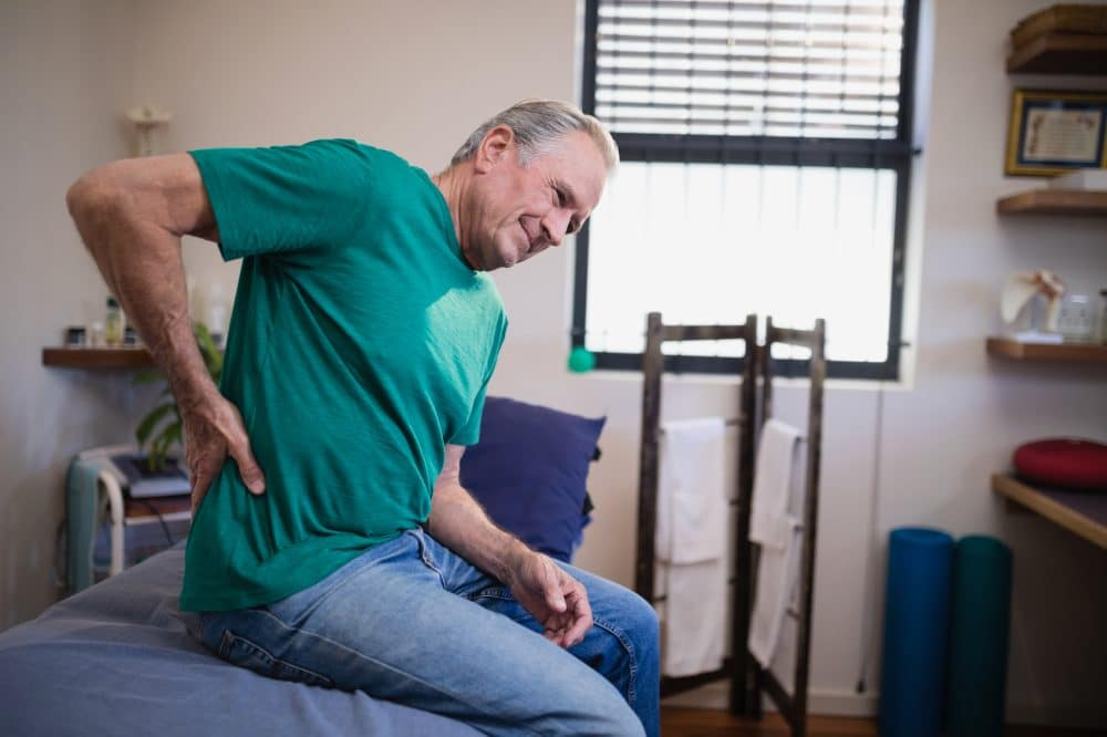 Elderly man holding his side due to pain