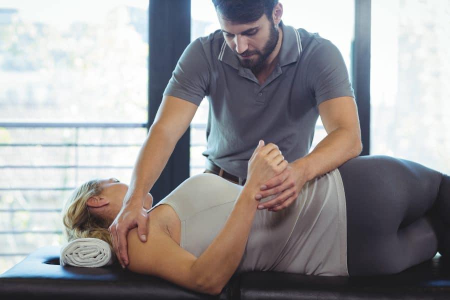 chiropractor adjusting patients back